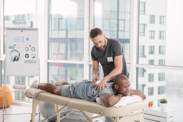 Terapeuta qualificado. médico legal profissional fazendo uma massagem nas costas do paciente enquanto faz seu trabalho Foto Premium