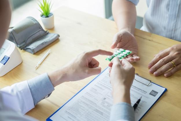 Terapeuta que consulta ao paciente masculino paciente sobre os comprimidos que escrevem sua droga de prescrição médica no escritório. Foto Premium