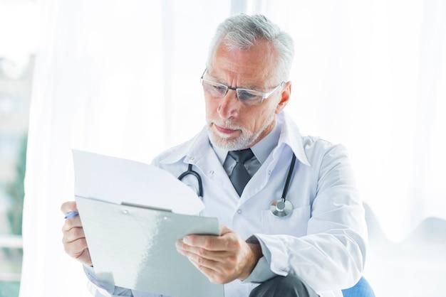 Terapeuta sênior examinando registros Foto gratuita