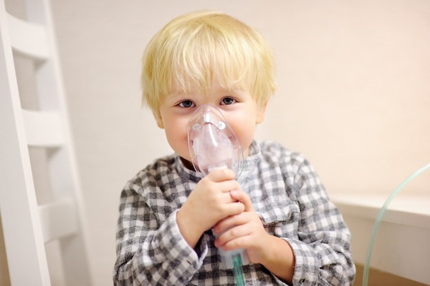 Terapia de inalação de menino bonito pela máscara de inalador. feche acima da imagem de uma criança com problema respiratório ou asma. menino doente com máscara de oxigênio clara. Foto Premium