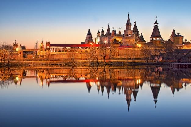 Teremki do kremlin izmailovsky em moscou com reflexo na água da lagoa à luz das luzes da noite Foto Premium