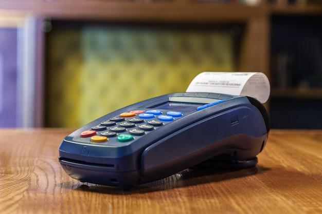 Terminal bancário com cheque impresso e botões coloridos em pé sobre uma mesa de madeira. o conceito de pagamento de contas no restaurante e loja, compras com cartão de crédito Foto Premium