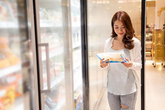 Terra arrendada bonita asiática nova alimento congelado no refrigerador no supermercado. escolhendo comida de conveniência em shopping Foto Premium