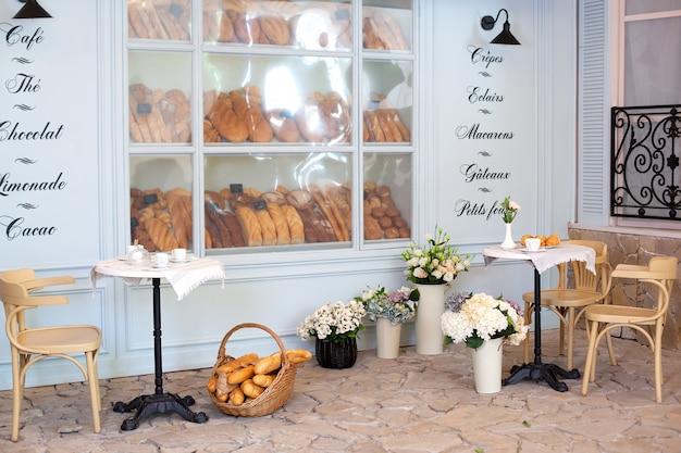 Terraço vazio de café e restaurante com mesas e cadeiras em estilo francês. bolos, pães e pão recém-assados em uma vitrine de padaria. rua café decoração, conceito interior. padaria de decoração. Foto Premium
