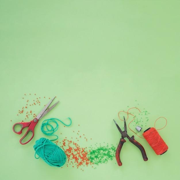 Tesoura; alicate; lã; grânulos e um carretel de fio laranja sobre fundo verde Foto gratuita