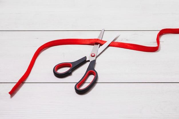 Tesoura com alças vermelhas corta a burocracia. a burocracia está mentindo sobre fundo de madeira. Foto Premium
