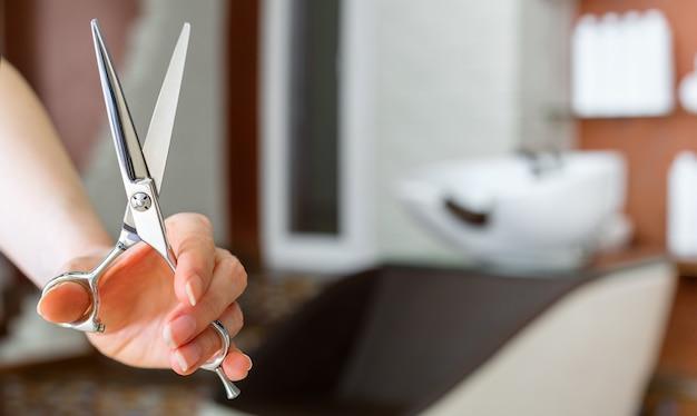 Tesoura de corte de cabelo em cabeleireiro mão contra pia de lavagem em salão de beleza, barbearia Foto Premium