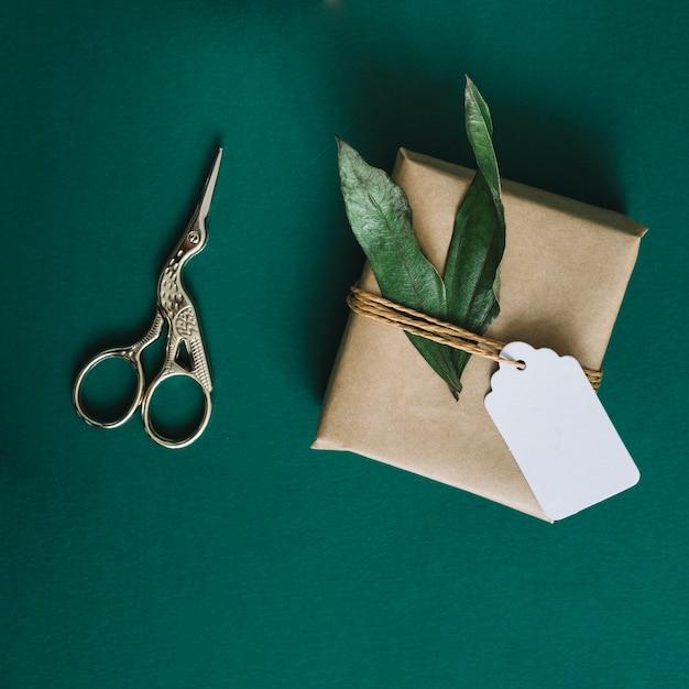 Tesoura de prata antiga; embrulhado presente com folhas e tag sobre fundo verde Foto gratuita