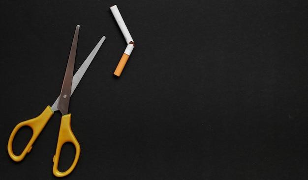 Tesoura e cigarro quebrado em fundo preto Foto gratuita