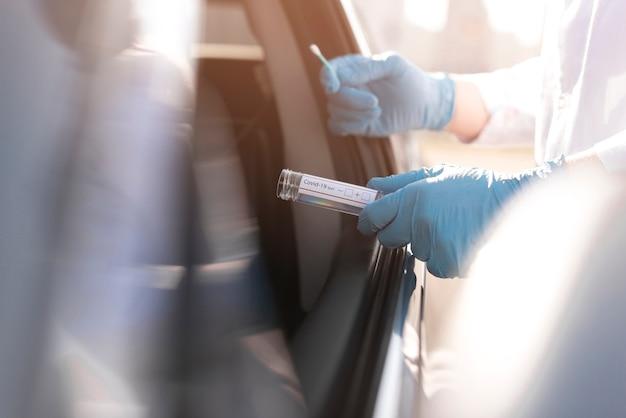 Teste de coronavírus e pessoa usando luvas ao lado de um carro Foto Premium