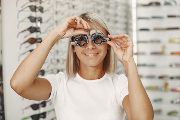 Teste de olho da senhora e exame de vista. menina fazendo exame de olho, com foróptero. mulher em uma camiseta branca Foto gratuita