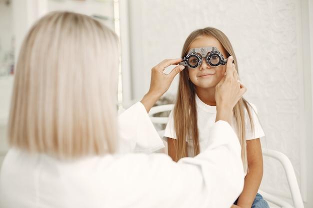 Teste oftalmológico infantil e exame oftalmológico. menina fazendo exame de olho, com foróptero. médico realiza exame de vista em criança Foto gratuita