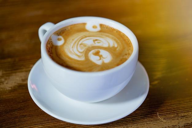 Teste padrão bonito sob a forma do urso em um copo branco com um latte maded no restaurante. Foto Premium