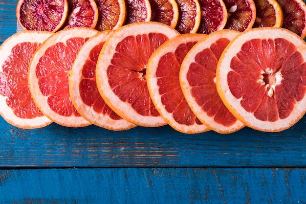 Teste padrão com fatias frescas de toranja, sobre a placa de madeira azul, com espaço da cópia. lay plana. Foto Premium