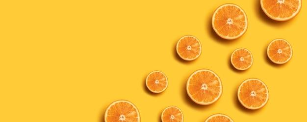 Teste padrão da fruta de fatias alaranjadas frescas no fundo amarelo. Foto Premium