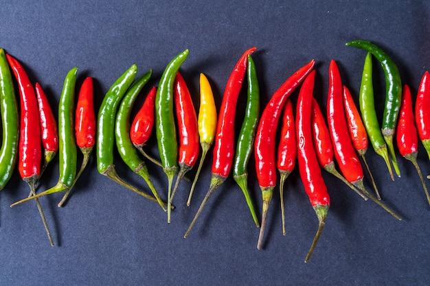 Teste padrão vermelho, verde e amarelo da configuração lisa das pimentas de pimentão sobre o fundo cinzento. Foto Premium