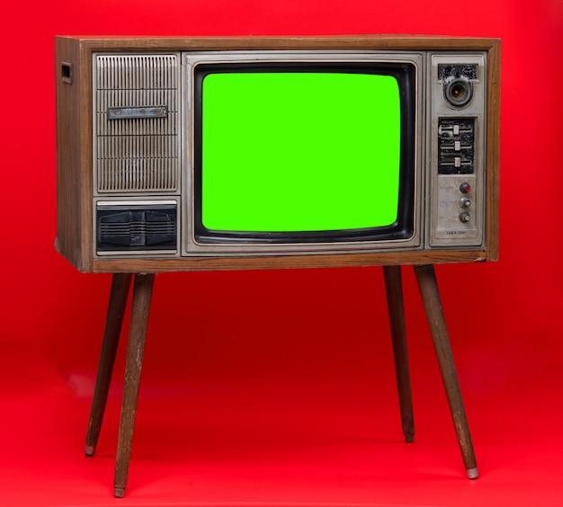 Tevê do vintage: aparelho de televisão retro velho isolado no fundo vermelho. Foto Premium