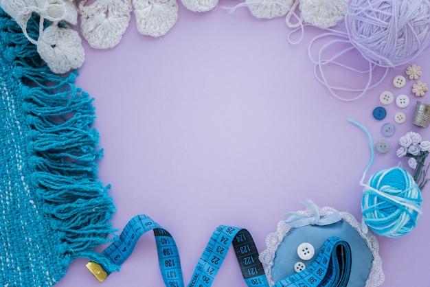 Têxtil tricotado; bola de lã; botão; fita métrica no fundo roxo com espaço de cópia para escrever o texto Foto gratuita