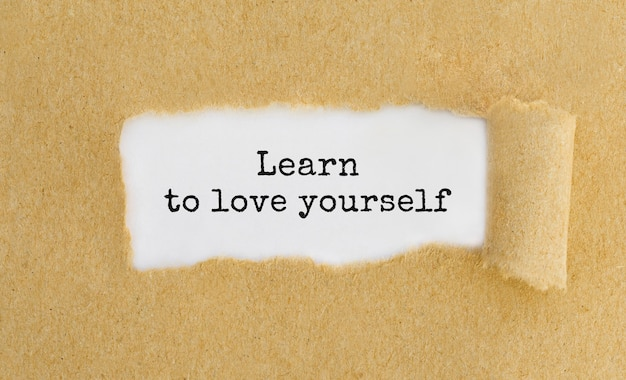 Texto aprenda a amar a si mesmo aparecendo atrás de um papel marrom rasgado Foto Premium