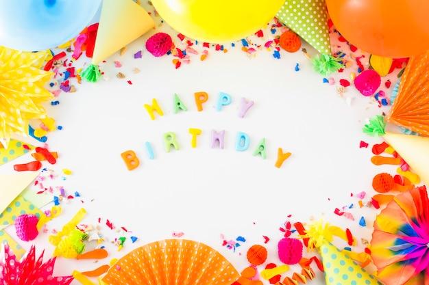 Texto colorido feliz aniversário rodeado com acessórios de festa em pano de fundo branco Foto gratuita