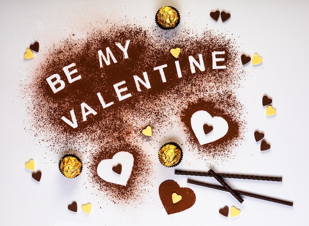 Texto com o conceito de dia dos namorados e três formas de coração de cacau em pó e bombons de chocolate Foto Premium