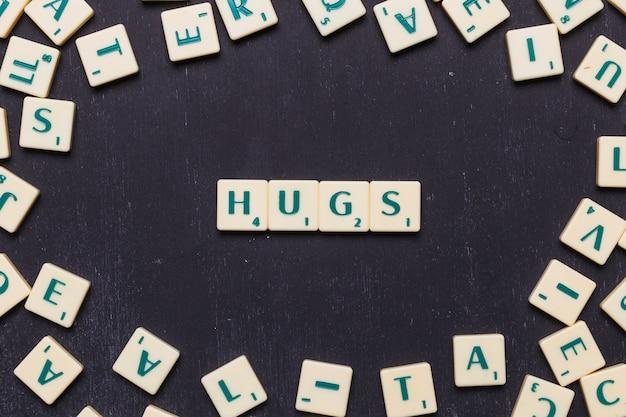 Texto de abraços dispostos em uma linha sobre fundo preto Foto gratuita
