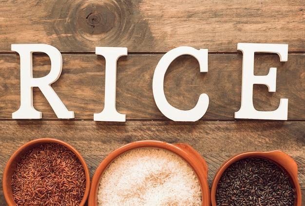 Texto de arroz branco com tigela de arroz na mesa de madeira Foto gratuita