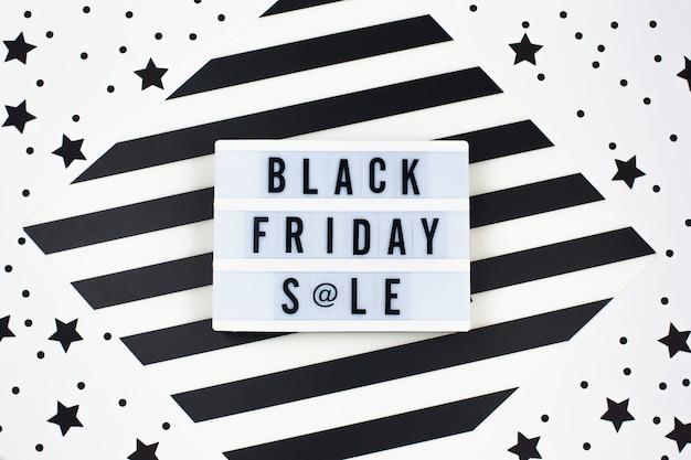 Texto de banner preto venda sexta-feira na mesa de luz branca e estrelas negras ao redor Foto Premium