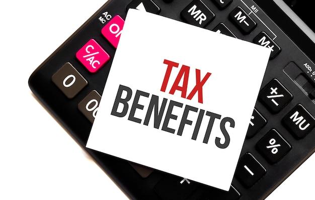 Texto de benefícios fiscais, escrito em uma nota que se encontra em uma calculadora e um fundo branco. lugar para texto Foto Premium