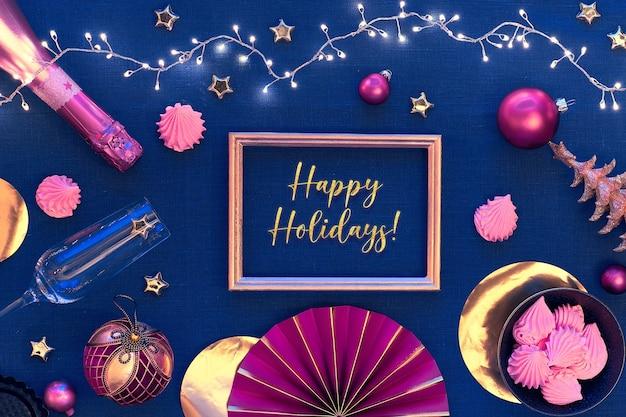 Texto de boas festas em moldura dourada. mesa de natal com pratos brancos, champanhe, utensílios dourados e decorações douradas vermelho-escuras. Foto Premium