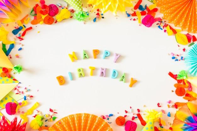 Texto de feliz aniversário com acessórios de festa no fundo branco Foto gratuita