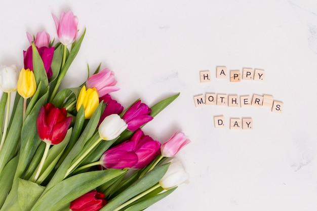 Texto de feliz dia das mães com flores tulipa colorida sobre fundo branco de concreto Foto gratuita