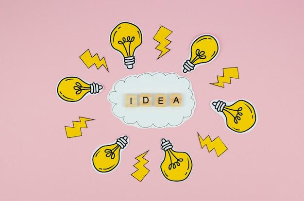 Texto de ideia na carta de rabiscos e lâmpadas em fundo rosa Foto gratuita
