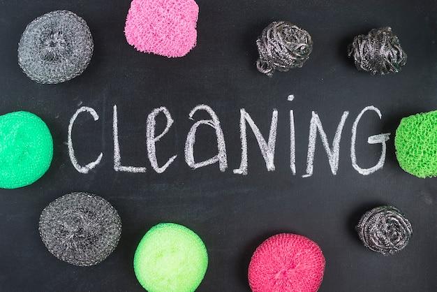 Texto de limpeza, rodeado por vários scrubs no quadro-negro Foto gratuita
