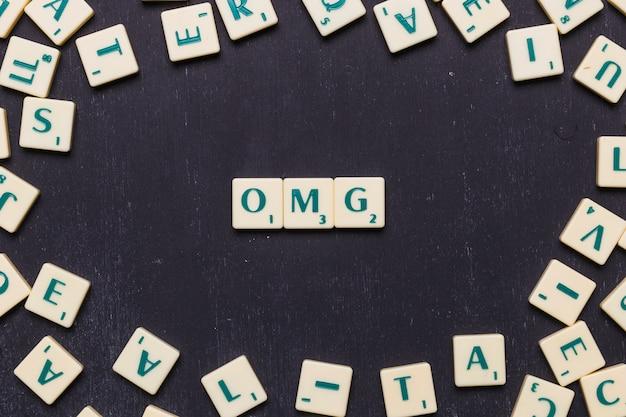 Texto de omg feito de cartas de jogo de scrabble Foto gratuita