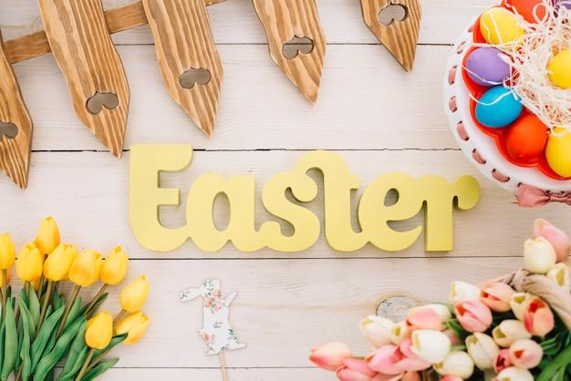 Texto de páscoa com cerca; coelheira; tulipas e ovos de páscoa coloridos no cakestand na mesa Foto gratuita