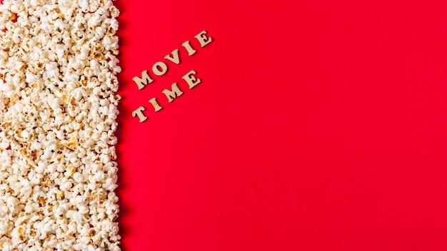 Texto de tempo de filme perto as pipocas em fundo vermelho Foto gratuita