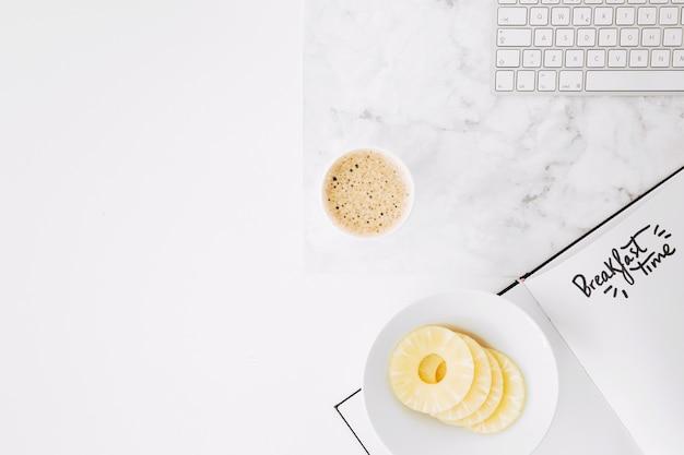 Texto de tempo de pequeno-almoço em papel com teclado; fatias de abacaxi e xícara de café na mesa Foto gratuita