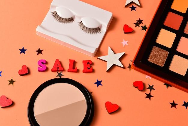 Texto de venda em um fundo laranja. produtos de maquiagem profissional da moda com produtos cosméticos de beleza, sombras, cílios, pincéis e ferramentas. Foto Premium