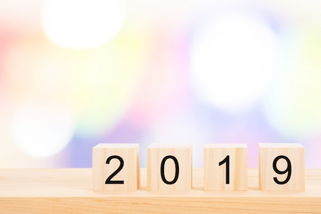 Texto do ano novo feliz 2019 em cubos de madeira na tabela de pinho de madeira e no bokeh claro do borrão. Foto Premium