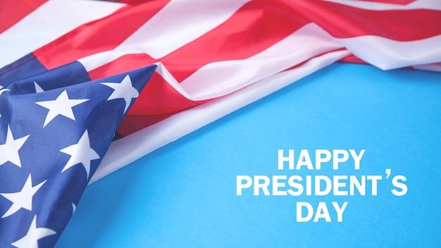 Texto feliz do dia do presidente em fundo azul com uma bandeira nacional dos estados unidos Foto Premium