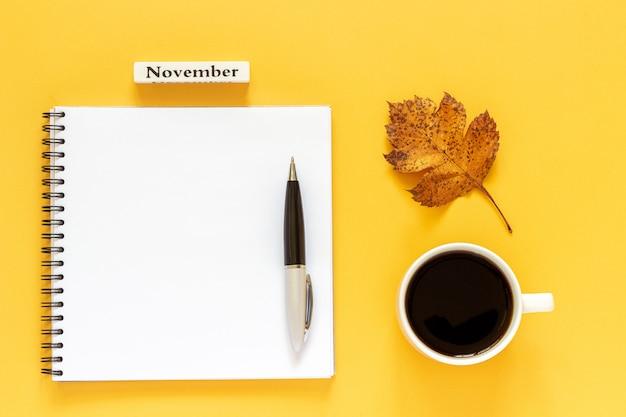 Texto novembro xícara de café, bloco aberto vazio com caneta e folha de outono em fundo amarelo Foto Premium