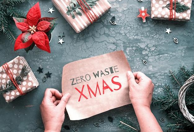 Texto zero waste xmas em papel artesanal. camada plana, vista superior em fundo cinza. presentes de natal diy e decorações feitas à mão. Foto Premium