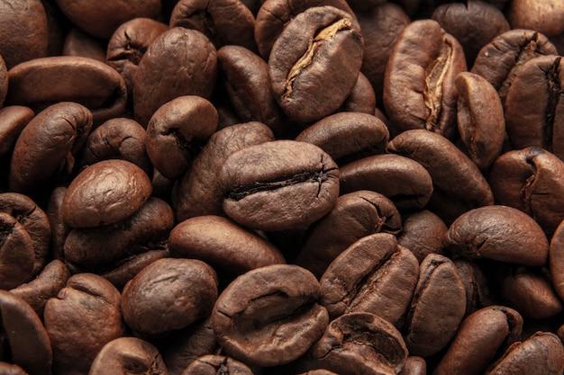Textura de fundo de um grande número de grãos de café torrados marrons perfumados e frescos. macro Foto Premium