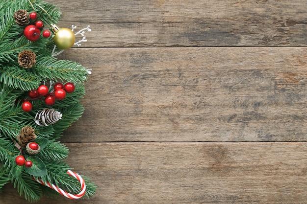 Textura de madeira antiga em branco decorar com folhas de pinheiro e cone, bolas de azevinho, bola de ouro e pirulito. Foto Premium