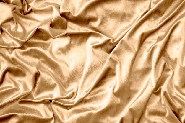 Textura de tecido de seda brilhante dourado Foto gratuita