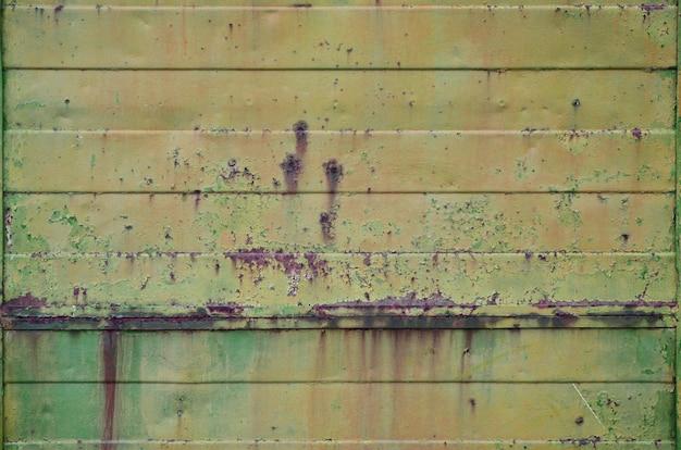 Textura de uma antiga parede de metal amarelo com danos significativos de exposição a condições climáticas desfavoráveis e umidade Foto Premium