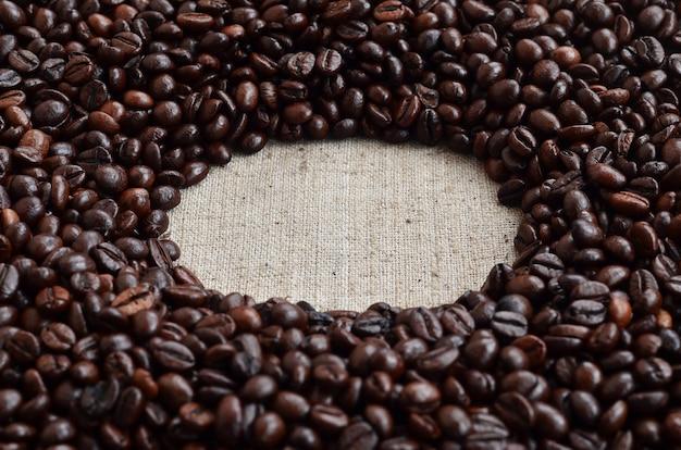 Textura de uma tela cinza feita de serapilheira velha e grossa com grãos de café sobre ele Foto Premium
