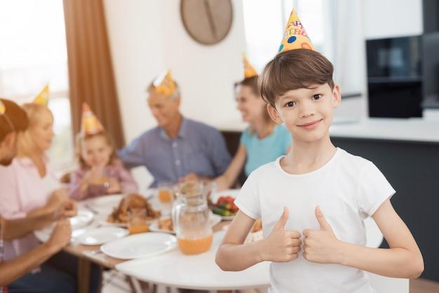 Thumbs up boy está posando contra o fundo da mesa festiva Foto Premium