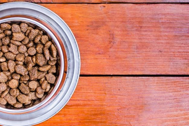 Tigela cheia de comida de cachorro no fundo de madeira com espaço de cópia Foto gratuita